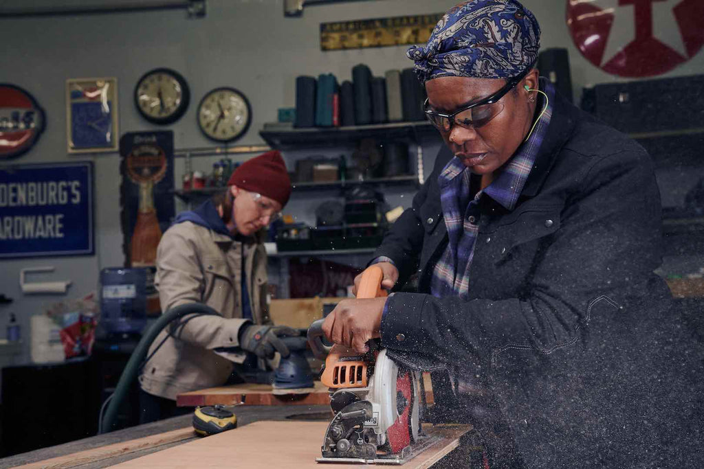 Dovetail Woman at Work electrical apprentice Isis Harris operating a saw in a workshop.