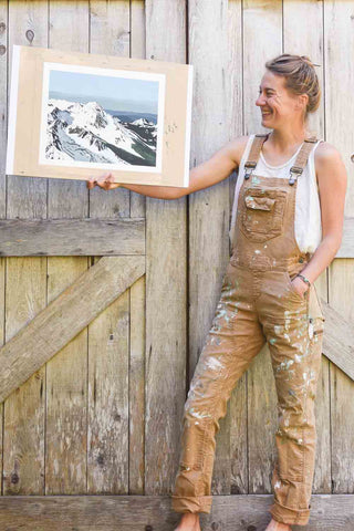 Nicole Freshley holding a landscape painting of snowy mountains while standing in front of a wooden barn door, wearing the Freshley Overalls in saddle brown canvas.
