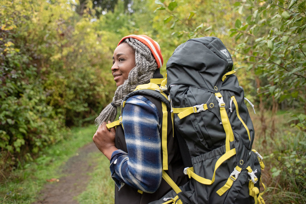 Mercy M'fon standing on the trail. She is a Black woman with grey locs braided into a larger braid, below an orange and white striped beanie. She is wearing a blue plaid Givens workshirt, a M'fon work vest, and carries a grey and yellow backpack.