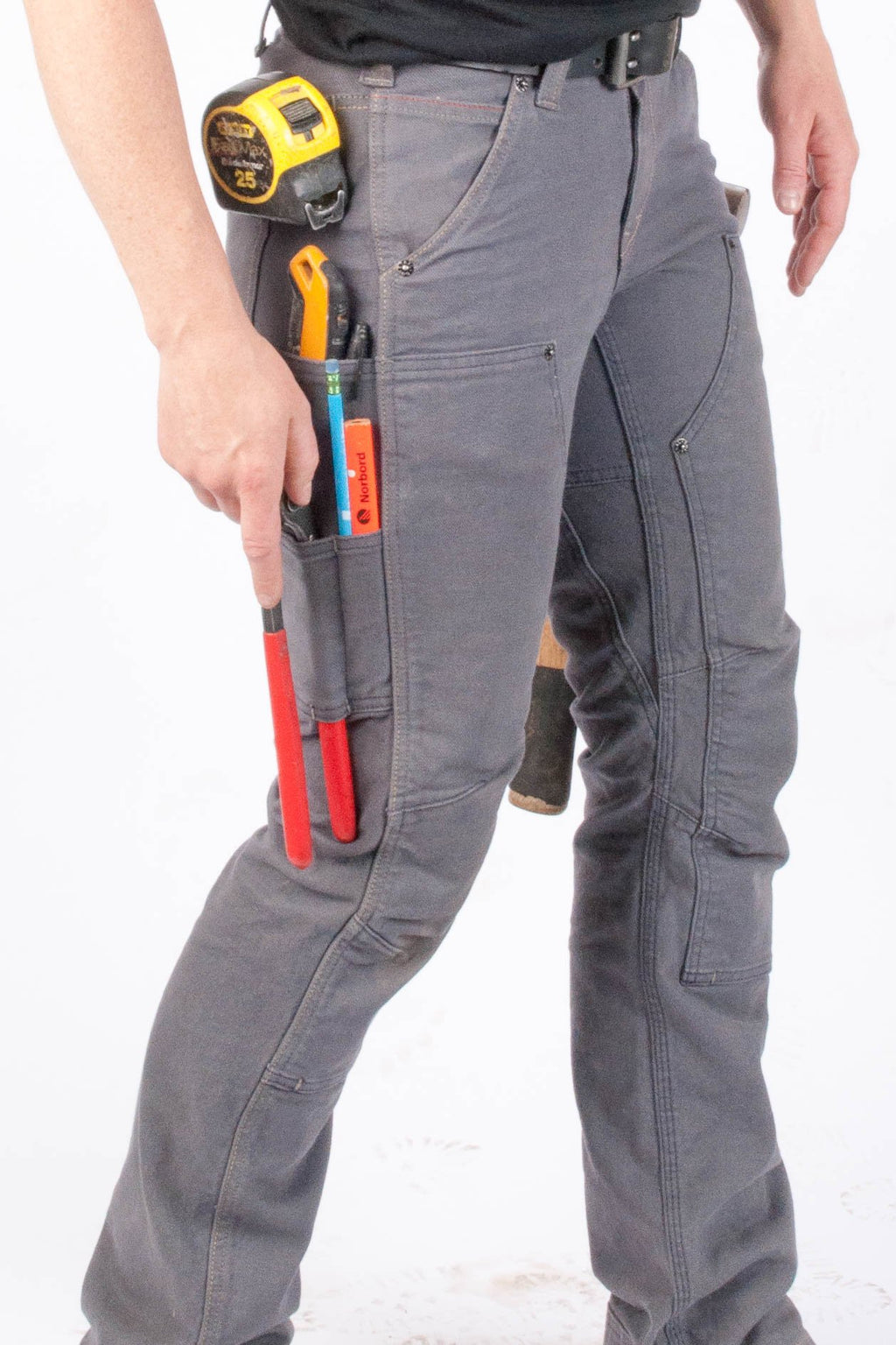 Lower half of Britt Smyton,  the namesake of the Britt Utility pant she is wearing. The Britt Utility Workpant for Women in Grey Stretch Canvas has a measuring tape, penci, plyers, hammer, and multiple tools in her side pockets on the right. On the left, the handle of a has a hammer can be seen popping out from The Britt Utility's modified hammer loop.