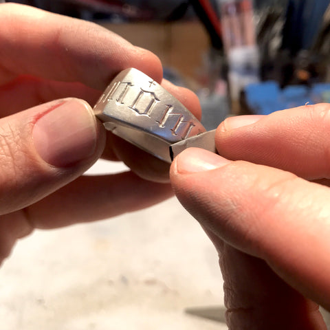 Silver signet ring being sanded with emery paper