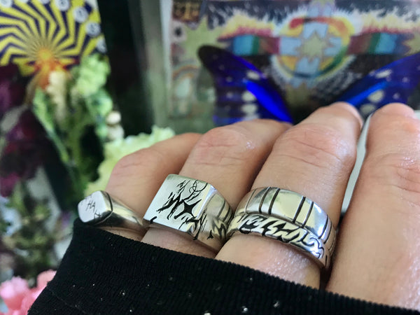 Carved rings on fingers with a colourful background