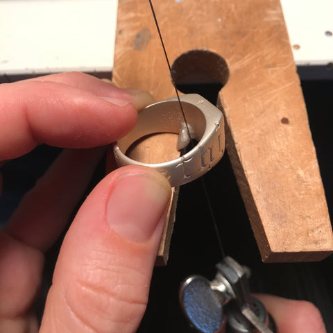 Silver signet ring with sprue being sawn on bench peg