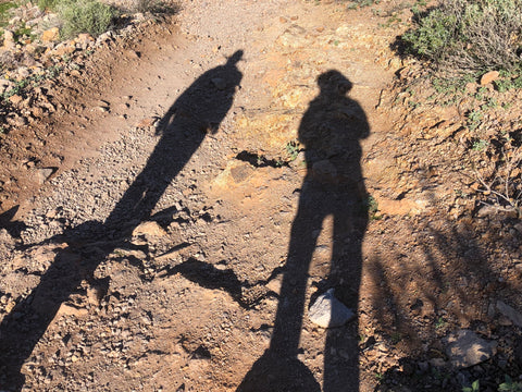 Shadows of two figures on dirt trail
