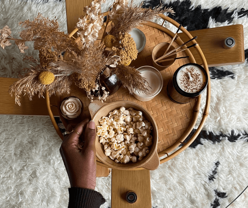 Renie Gray for Basket Finds, an interview by La Basketry. Image showing a rattan tray topped with dried flowers, a bowl of popcorn and other decorative items