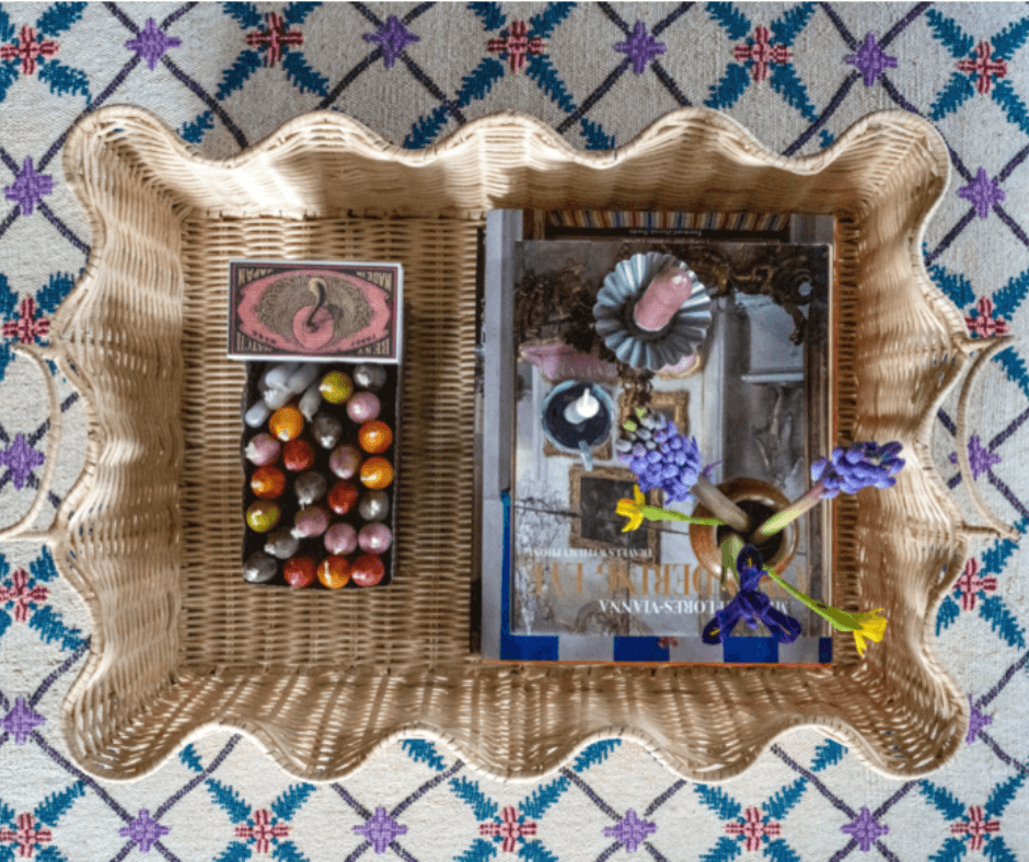 Top down view of a rattan ripple tray filled with candles, a magazine and flowers against a vintage patterned carpet, by Lisa Mehydene, founder of edit58. Image for her interview with La Basketry