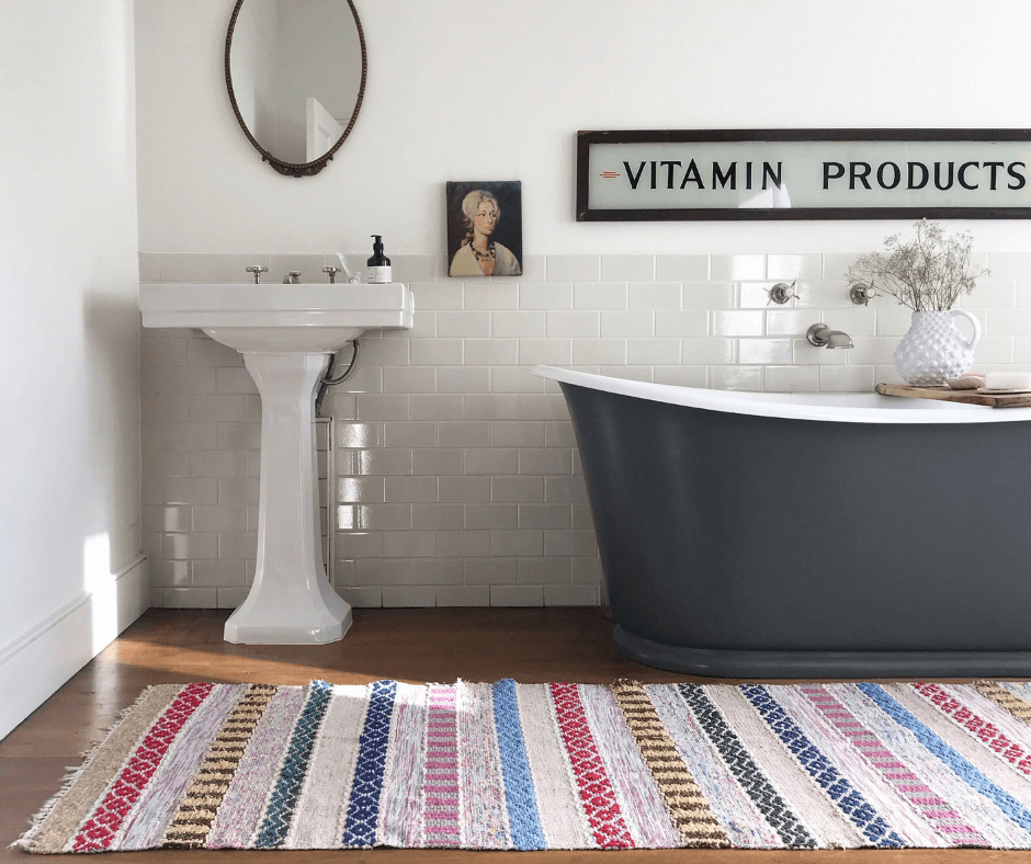 Deep grey bath tub in a white bathroom with a bright coloured striped rug from edit58 founded by Lisa Mehydene. Image for her interview with La Basketry