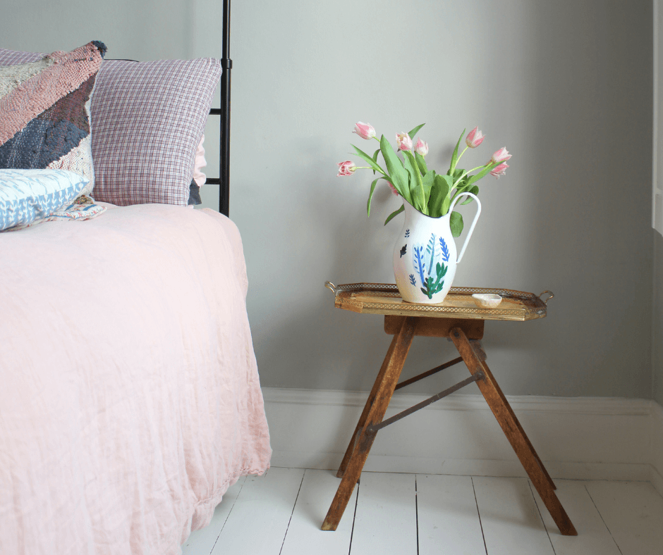 Close up of a bedside wooden table next to a bed with baby pink bedding, with a white vase decorated with blue flowers filled with pink tulips, from Lisa Mehydene, founder of edit58. Image for her interview with La Basketry