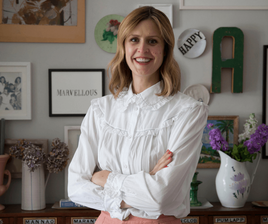 Lisa Mehydene, founder of edit58 wearing a white shirt and pink trousers in front of a wall of picture frames. Image for her interview with La Basketry