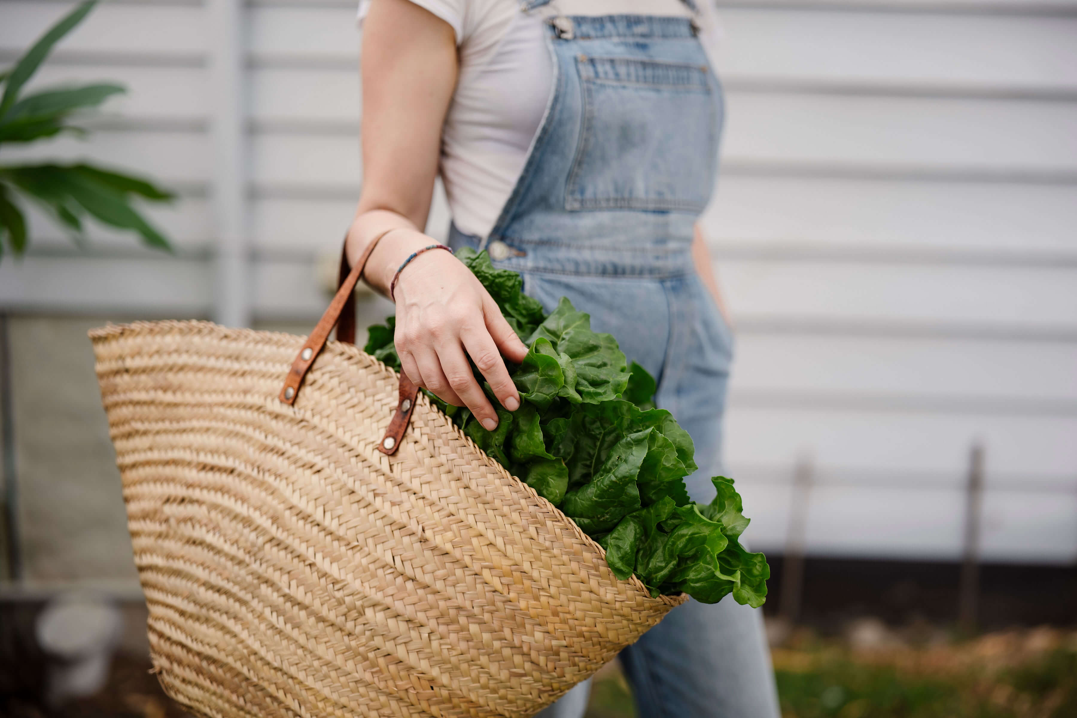 Sarah Bell, founder of Stackwood concept store Australia holding a basket bag with salad leaves in for La Basketry on the shelf