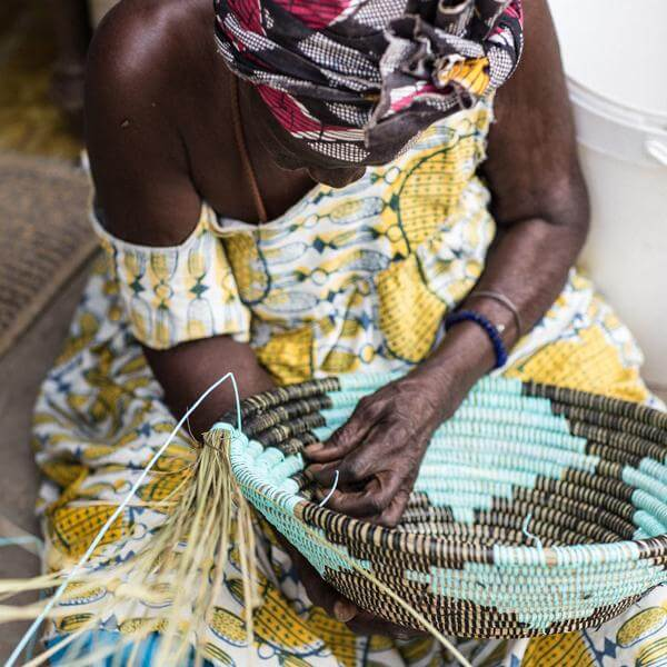 a senegalese lady basket weaving a large blue basket bowl
