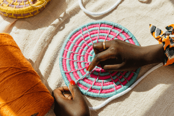 hands weaving a circle placemat in blue and pink by la basketry