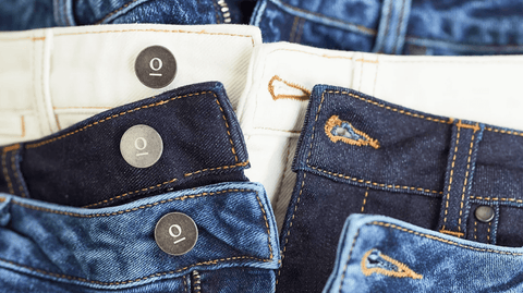 la basketry for denim kind thought clothing - a stack of jeans in different coloured denim