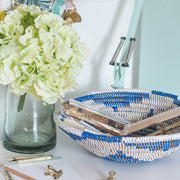 la basketry handwoven storage bowl in blue and white pattern shown  on a desk with stationery and flowers