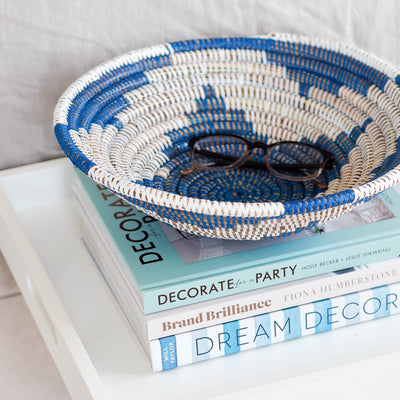 la basketry handwoven storage bowl in blue and white pattern shown on a tray with books
