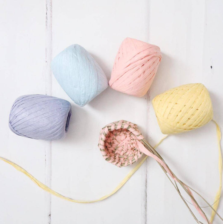 a flat lay of four pastel coloured rolls of eco-friendly paper raffia, in lavender, blue, pink and yellow, for use when diy crafting and coiling baskets. shown with a miniature basket in pink by la basketry