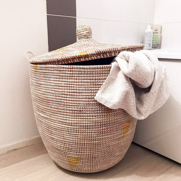 an extra large storage or laundry basket in natural weave and yellow, with a towel hanging out. by la basketry
