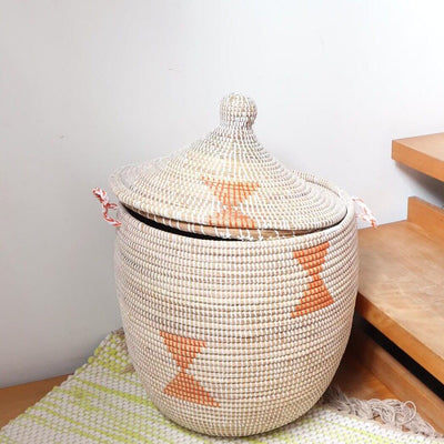 a beautiful handwoven grand large storage basket in natural weave with orange patterns. a lidded storage basket for laundry, accessories or a plant from la basketry