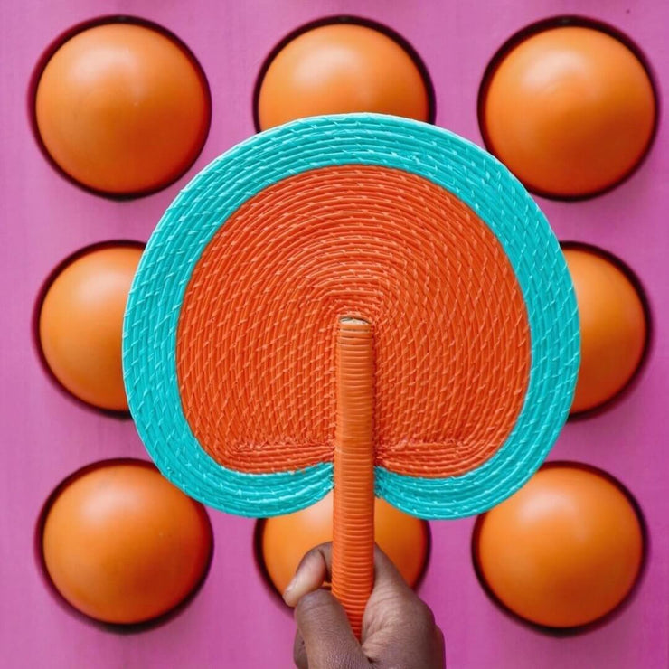 a handwoven fan by la basketry in orange and turquoise