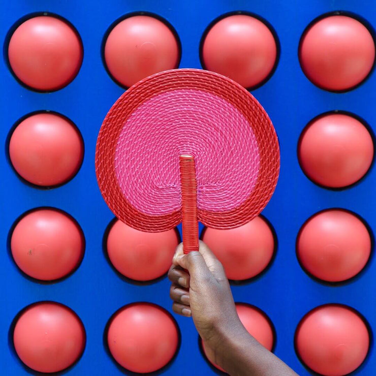 a handwoven fan by la basketry in pink and red
