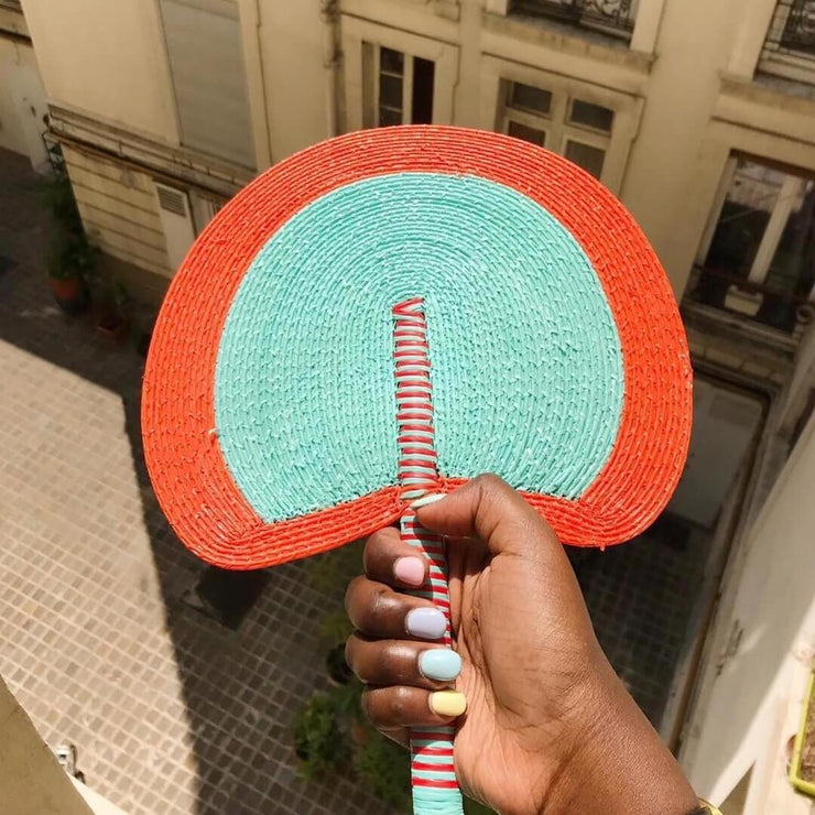 a handwoven fan by la basketry in turquoise and orange
