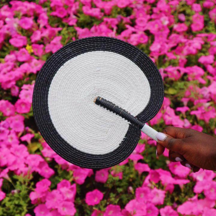 a handwoven fan by la basketry in white and black