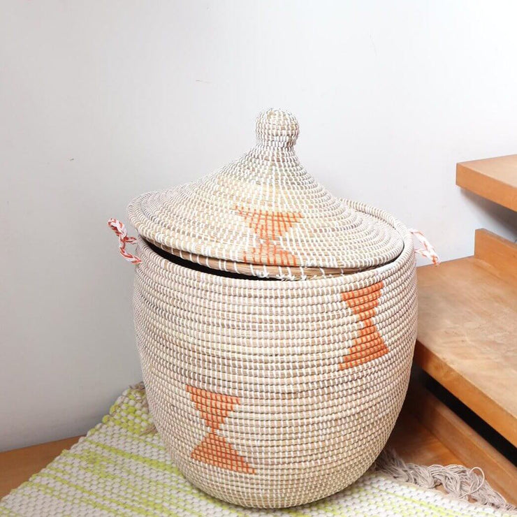 a beautiful handwoven large storage basket in natural weave with orange patterns. a lidded storage basket for laundry, accessories or a plant from la basketry