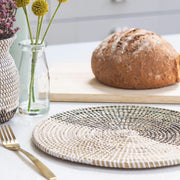 a beautiful handwoven african placemat in natural weave with black and white recycled plastic weaved through in half white, half black. by la basketry, shown in a breakfast setting with weaved vase and flowers