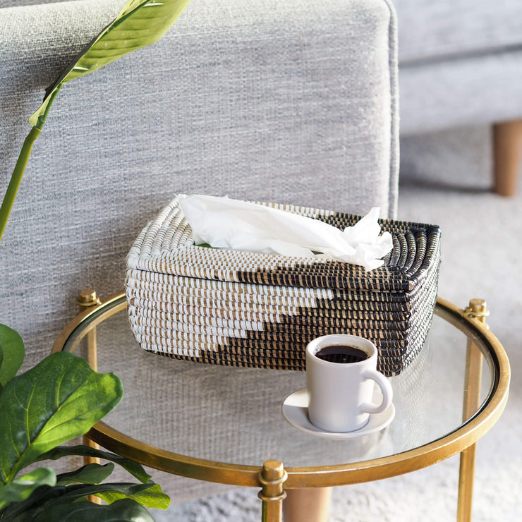 la basketry handwoven tissue box in black shown on a table with coffee in living room