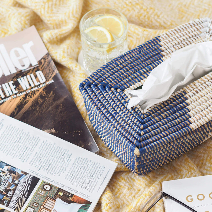 la basketry handwoven tissue box in blue on a bed with magazines and a drink