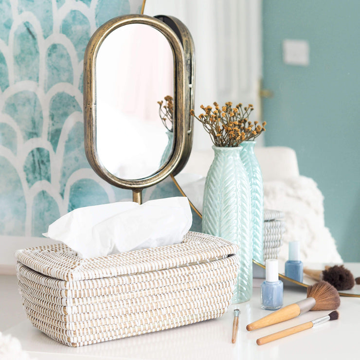la basketry handwoven tissue box in white shown in a bathroom with makeup items and blue vase