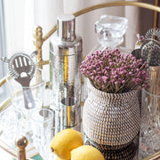 la basketry handwoven vase in white and black weave filled with purple flowers, on a bar trolley with cocktail making kit and lemons