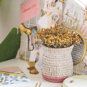 la basketry handwoven vase in white and pink weave with yellow flowers, shown on a desk with stationery