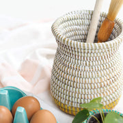la basketry handwoven vase in white and yellow weave filled with kitchen utensils, shown on a counter with a box of eggs and small basket with a plant in