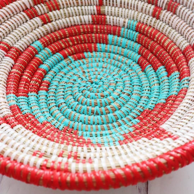 la basketry anta storage bowl close up in red white and turquoise with beautiful woven star pattern, handmade by artisans in senegal