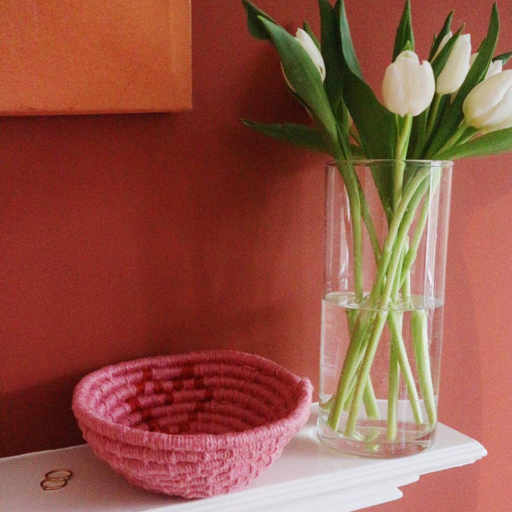 la basketry galentines day limited edition twine basket kit in pink and red with love heart motif shown on a shelf with white tulips and an orange wall