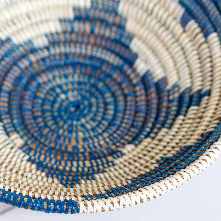 la basketry handwoven storage bowl in blue and white pattern shown close up highlighting the weave of natural grasses and plastic strips