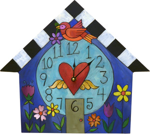 """A Little Birdie Told Me"" House Clock – A bird is perched on a home with flower beds out front front view"