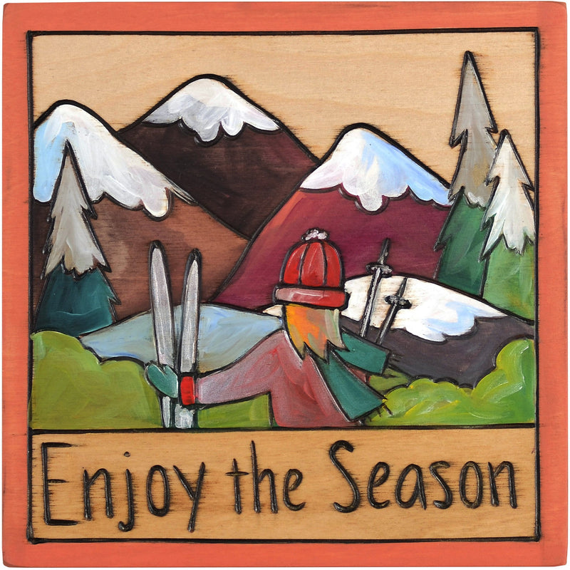 "7""x7"" Plaque –  ""Enjoy the Season"" plaque with girl and ski gear in front of the mountains motif"