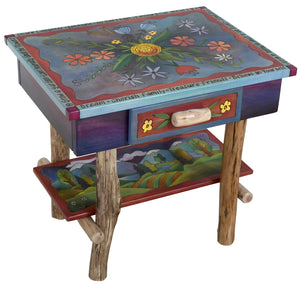 Nightstand with Open Shelf –  Eclectic folk art nightstand with birch legs and shelf designed with floral motifs and rolling mountain landscape