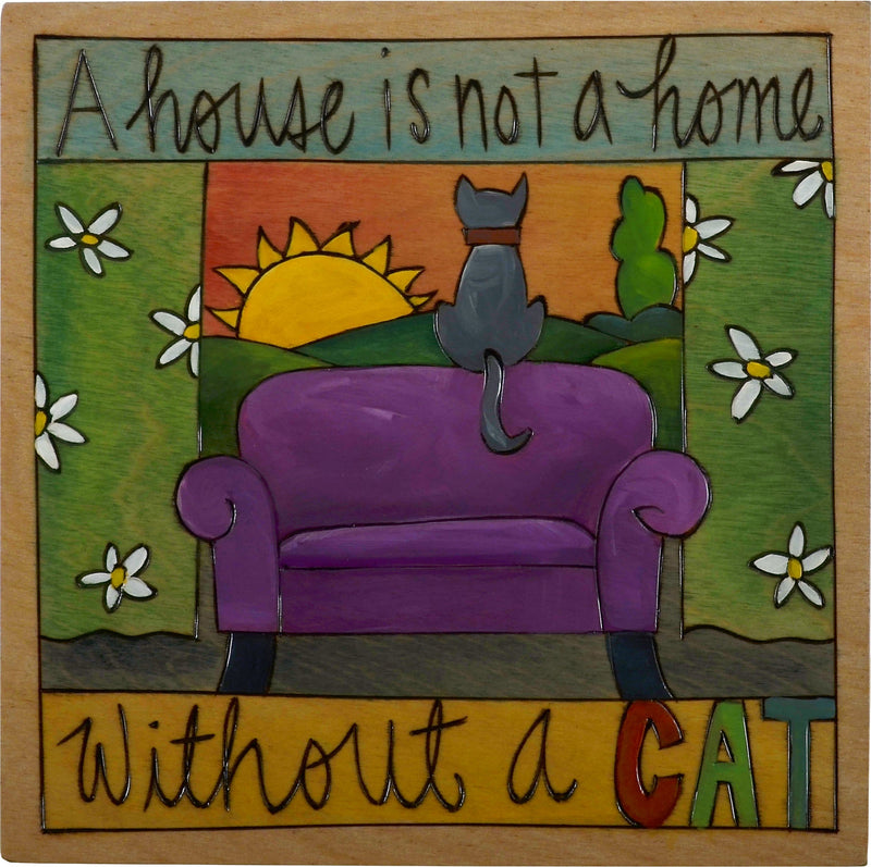 "Sticks handmade wall plaque with ""A house is not a home without a cat"" quote and cat sitting by the window living room scene"