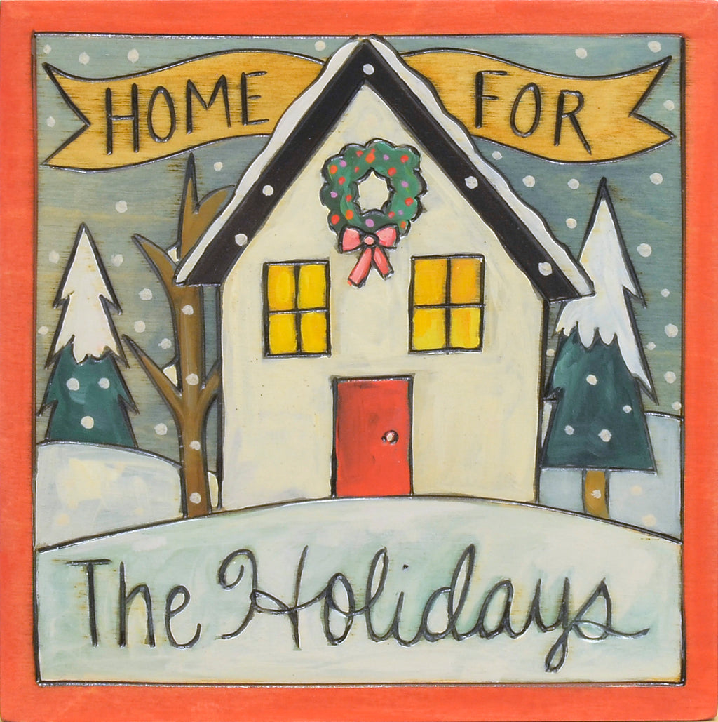 """Home for the holidays"" plaque with a cute house adorned with a wreath"