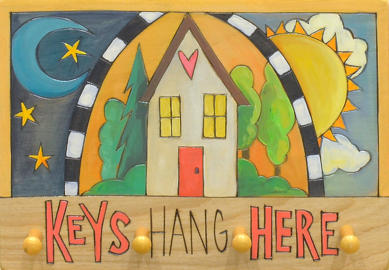 """Keys hang here"" plaque with a home splitting a curtain revealing a sun and moon"