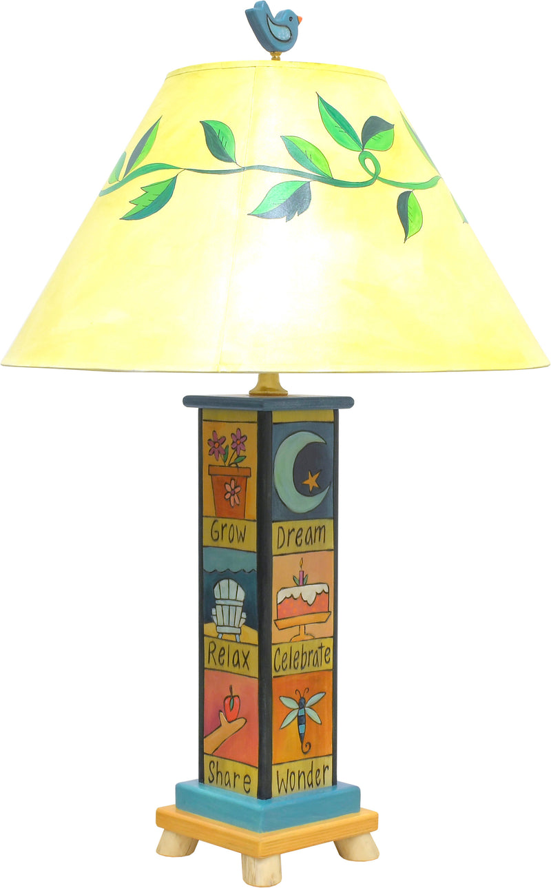 Fun and folky table lamp with vine-wrapped shade, bird finial, and base with cute boxed icons and coordinating phrases, back view