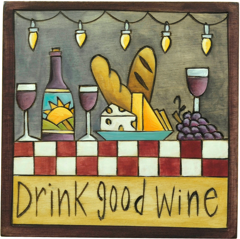 """Drink good wine"" plaque with wine and cheese on a patio under string lights"