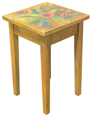 Beautiful natural wood toned end table with pink floral spray on top