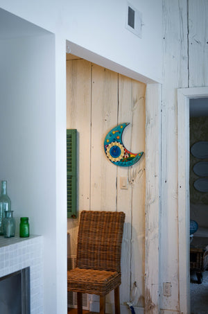 Moon shaped Sincerely, Sticks printed clock hung on barn wood wall in a home