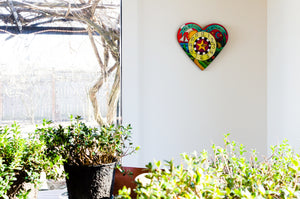 """Loving Time"" Heart Clock – A landscape design fills this heart shaped clock displayed in a home's sunroom"