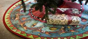 """Run, Run, Rudolph"" Tree Skirt – Rudolph and his reindeer crew circle around a starry-sky landscape on our canvas tree skirt displayed under a tree with presents"