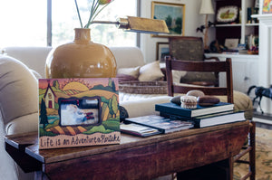 """Grandma's House"" Picture Frame – ""Life is an Adventure, Partake"" frame with home and sunset on the horizon motif displayed on an end table"